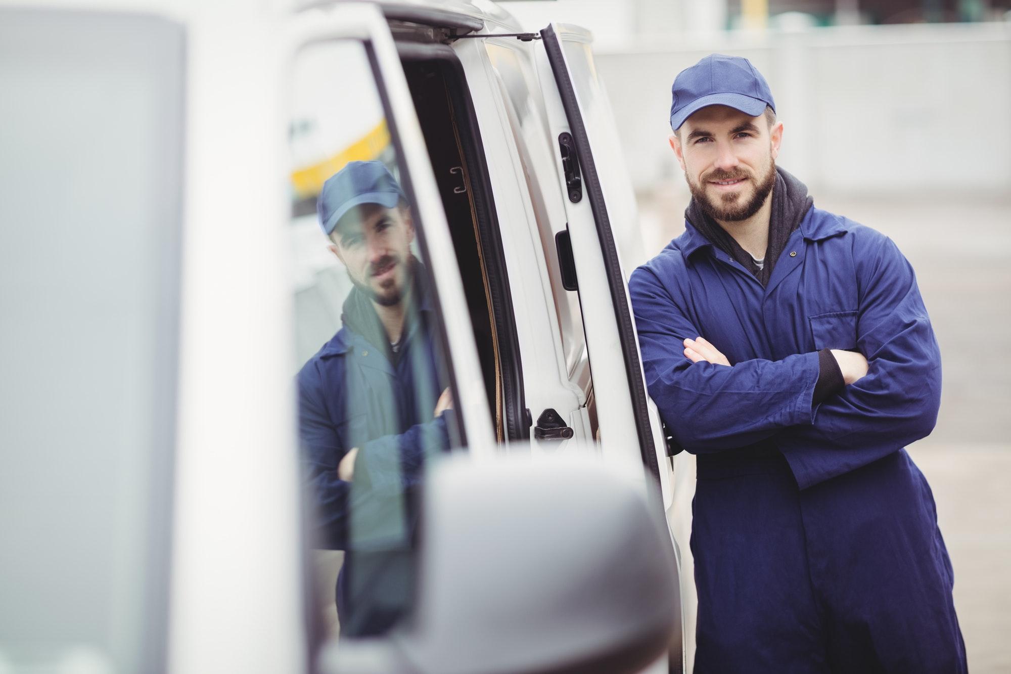 Repairman with arms crossed leaning against his van